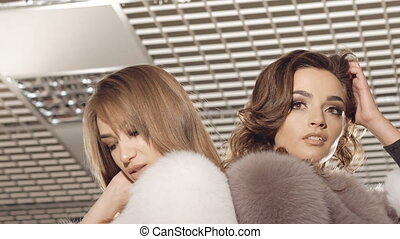 Two girls posing in fur coats in fashionable rich boutique. Slowly