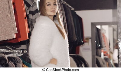 Sexy woman flirting seductive in rich fur coat for camera....