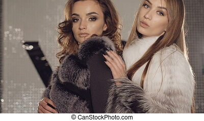 Two models stands in pose in fur coats in fashionable rich boutique. Slowly