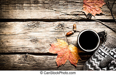 Autumn style. A Cup of hot coffee with mittens. On a wooden...