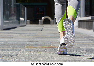 Woman running outdoor in the city, sunlight