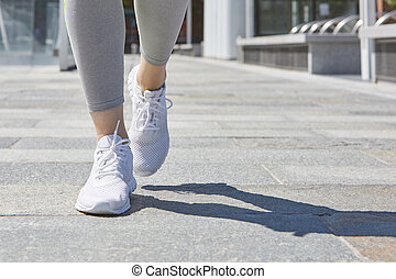 Woman running in a sunny city, close up on shoes