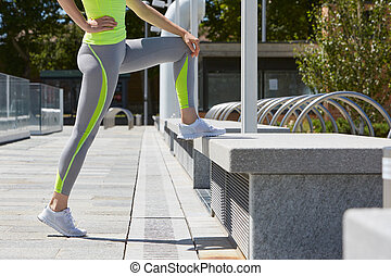 Woman stretching after run in the city, sunny day - Woman...
