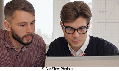 Man in eyeglasses explaines something on laptop to his male colleagues