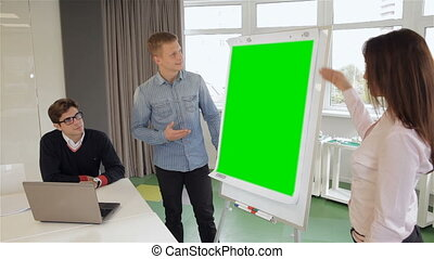 Man and woman show something on flipchart - Blond man and...