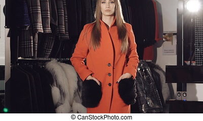 Rich lady catwalking in red fur coats in the rich boutique....