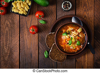 Minestrone, italian vegetable soup with pasta on wooden...