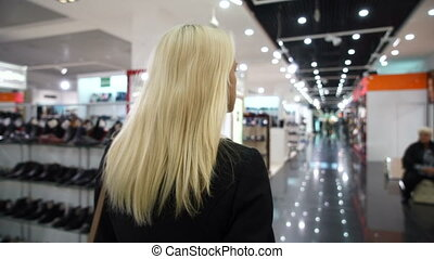 Beautiful blonde goes along the shop windows - shopping -...