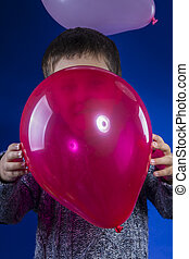 Red ballon, child playing with colored balloons at a birthday party happy