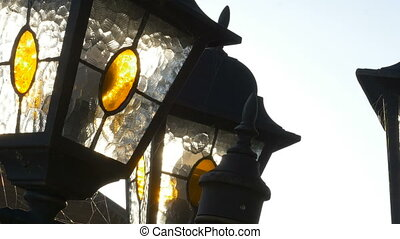 A street lantern is in the rays of a sun