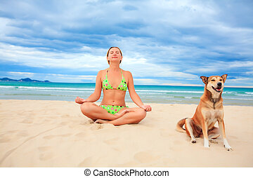Meditating - Woman with dog are meditating on the tropical...