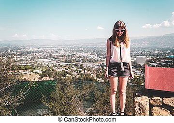 Girl at Hollywood Hills with panoramic view of Los Angeles -...