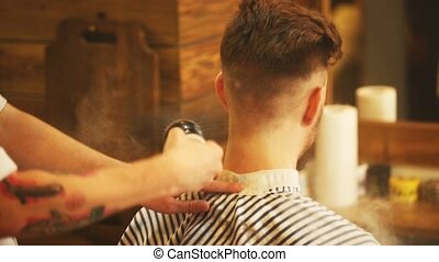 Barber making haircut of attractive man in barbershop