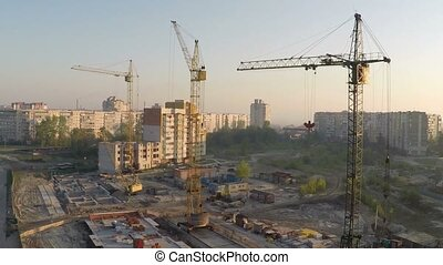 Industrial construction cranes and building silhouettes over...