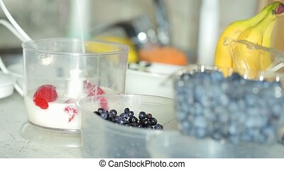 Preparation smoothie with strawberries, banana, blueberries...