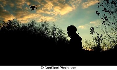 Man manages drone. Silhouette against the sunset sky