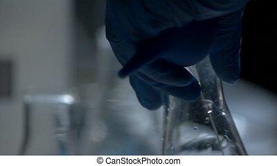 Hand in glove holding beaker.
