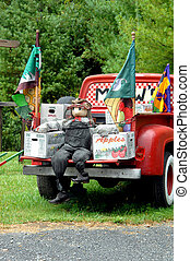 Advertising Apples - Scarecrow sits on tailgate of red...