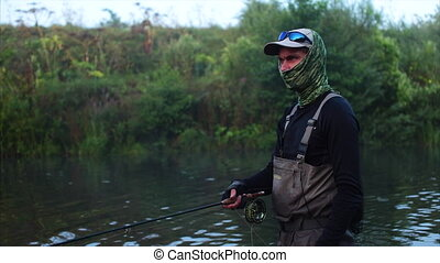 Fisherman goes fly fishing in the morning river