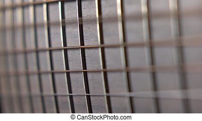 Trembling guitar strings against fret. Music performance. 4K...