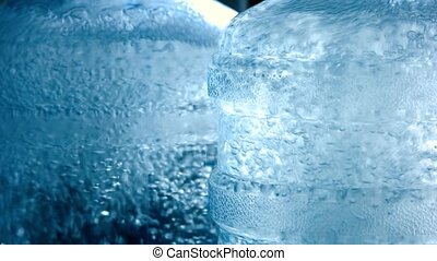 Big bottles with water. Bubbles in liquid. Drinking water of...
