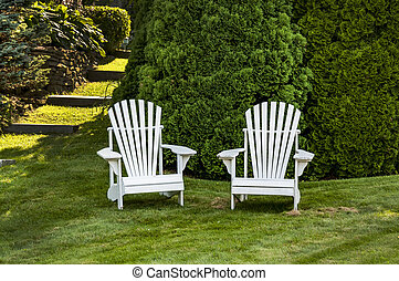two adirondack chairs on the grass in Maine, USA