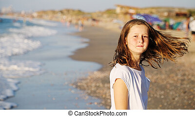 portrait of a real 10 years old girl walking on the beach