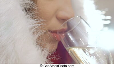 Closeup of sexy woman dressed in snow-maiden suit drinking...