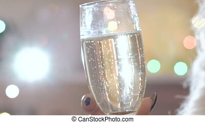 Two glasses with champagne toasting over holiday blinking...