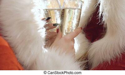 Two girls in snow maiden suit holds bocals of champagne in...