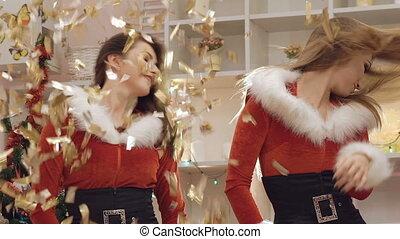 Happy women dancing in falling gold glitter . Slowly
