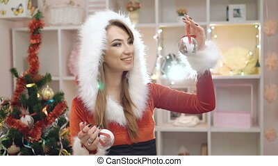 Happy woman dressed in glamour suit smiling and using Chirstmas toy in 4K