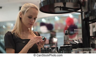 Beautiful girl is considering make up at the mall -...