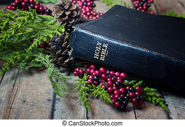 An Old Rustic Bible with Christmas Garland on a wood plank...
