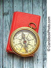 Red closed book with retro compass on wood