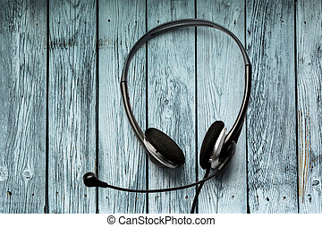 Headset with microphone on the wooden background