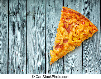 Slice of home pizza with cheese on wooden background