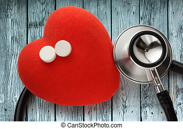 Red heart, stethoscope and pills on wooden background