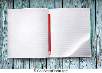 Opened notebook with pencil on the wooden background