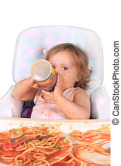 Messy baby girl drinking juice and eating spaghetti - Young...