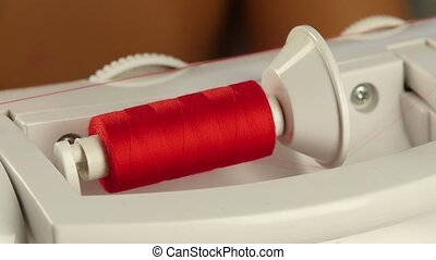 Spool of red thread. Slow motion - Spool of red thread,...