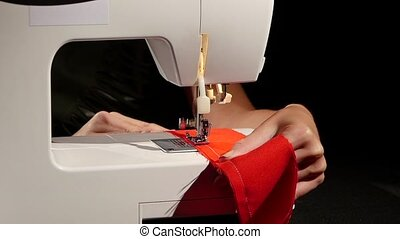 Sew a red cloth. Slow motion - Sew a red cloth, woman sews...