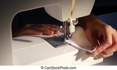 Sew a white cloth. Slow motion - Sew a white cloth, woman...