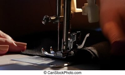 Girl sews on the sewing machine. Slow motion - Girl sews on...