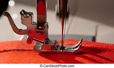 Sewing machine sews a zigzag stitch on the red fabric. Slow...