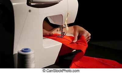 Sew red fabric. Slow motion - Sew red fabric, woman sews on...