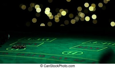 Many poker chips falling on green casino table, gambler...