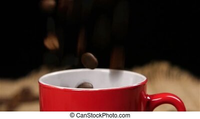 Coffee beans falling into red small cup. Slow motion -...