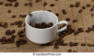 Coffee beans are falling in a coffee cup. Slow motion