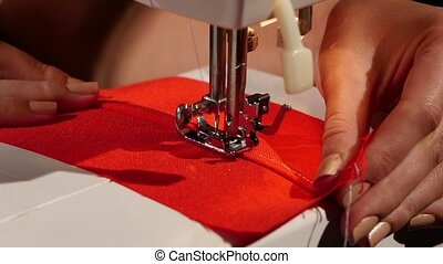 White stitch on a red fabric. Slow motion - White stitch on...